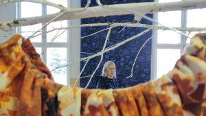 Paola Suhonen suuressa näyttelytilassa keskellä erilaisia kankaita.