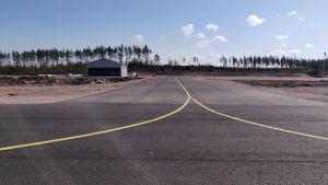 Bild på en landningsbana som förgrenar sig och en byggnad som står intill.