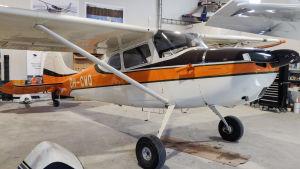 Ett litet flygplan i vitt och orange.