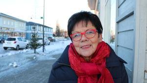 En kvinna med mörkt hår och röda glasögon. Runt halsen har hon en stor röd halsduk.