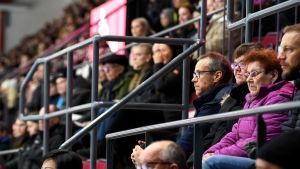 Pasi Mustonen sitter på ishockeyläktare bland publik.