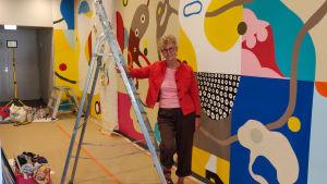 En kvinna i rött lutar sig mot en metallstege. Bakom henne syns en färggrann abstrakt väggmålning.