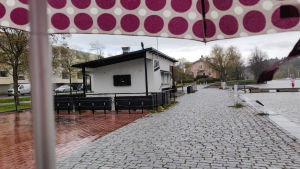 En stängd uteservering invid Borgå å. I övre hörnet syns kanten av paraplyt som fotografen står under.