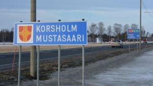 Skylt med texten Korsholm i förgrunden och skylt med texten Vasa i bakgrunden.