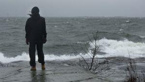 En människa står på ett berg och tittar ut över stormande hav i Helsingfors.