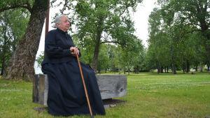 En kvinna sitter på en bänk i en svart dräkt och med en käpp i handen. I bakgrunden syns en park med höga träd.