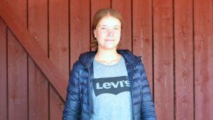 Halvbild på Erika Gröning, en ung kvinna med långt mörkt hår, i blå jacka och Levis-tröja.
