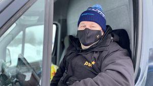 Juhani Kantola sitter framför ratten i sin bil.