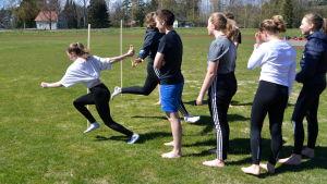 Elever från Lovisanejdens högstadium övar masstafett på gräsplan.