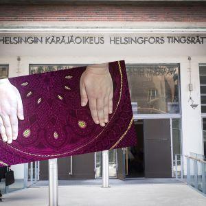 Två händer på en matta inklippt framför Helsingfors tingsrätts byggnad.