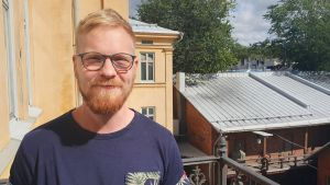 Blond man med glasögon står i solen.