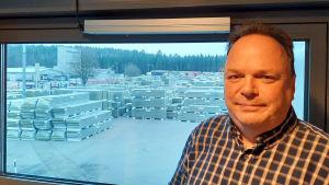 Tom Österlund, en man med rutig skjorta, står framför ett fönster. Där ute finns högar med byggelement.