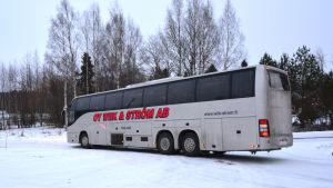 Buss som körs av bolaget Wiik & Ström på en parkering. Vinter.