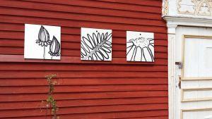 Tre kvadratiska tavlor med grafiska avbildningar av blommor och blad, upphängda mot en röd träfasad.