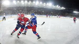 Två hockeyspelare kämpar om pucken.