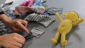 Hand som klipper till ett par docktrosor av en strumpa. En docka ligger också på bordet samt en hög med gamla strumpor.