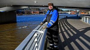 En man, iklädd blå halare, står och fiskar med metspö under en bro.
