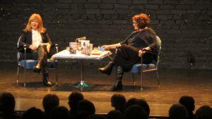 Malou von Sievers och Monika Fagerholm samtalar på en scen. Många i publiken tittar på.