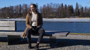 Ung kvinna sitter på bänk vid havet.