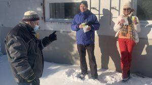 En man med ansiktsmask talar med en man och en kvinna som står och dricker kaffe utomhus vid en husvägg.