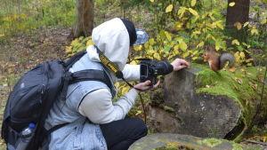 Fotograf med kamera ger nötter åt en ekorre.