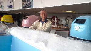 En man står mellan två motorbåtar inne i en utställningshall.