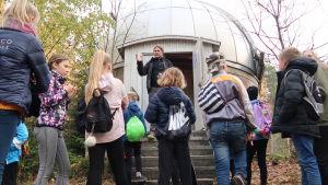 Pasi Nurmi står framför en grupp elever vid ett stjärnobservatorium.