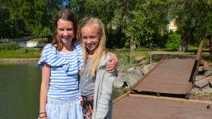 Två flickor håller om varandra på en brygga.