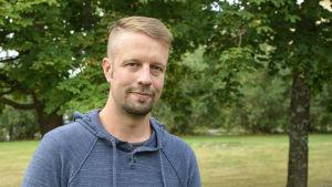Fredrik Kullberg, rektor för arbis i Vasa, tittar in i kameran. I bakgrunden grönskande träd.