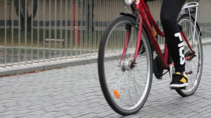 En röd cyklist cyklar över biblioteksbron i Åbo.