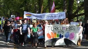 Flera personer går i en pridemarsch med banderoller vid åstranden i Åbo.