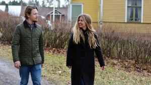 Oscar Gräsbeck och Ida Söderström går utanför ett stort gult trähus.