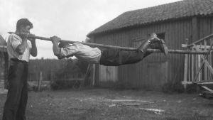 En man håller i en stång med två händer och sina fötter och hänger i den. Bilden är tagen 1930 i Sund, Åland.