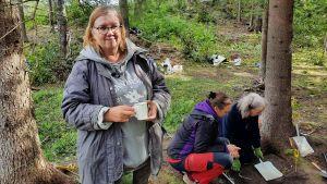En kvinna står i en skog med en kaffemugg i handen. Bredvid henne sitter två kvinnor på huk bredvid en grop.