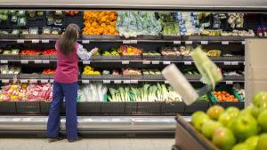 Ett butiksbiträde vid grönsakshylla.