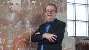 Richard Tellström står framför en brun vägg.