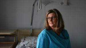 Kvinna sitter på en sjukhussäng och tittar snett över axeln ut genom fönstret.