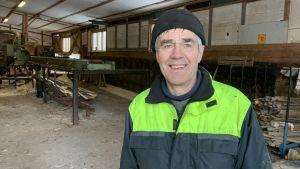 En man i arbetskläder står intill ett sågverk.