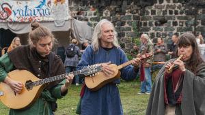 Kolme muusikkoa soittaa soittimiaan keskiaikamarkkinoilla keskiaikaiset vaatteet yllään.