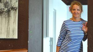 Blond kvinna i blåvit randig skjorta i en dörröppning.