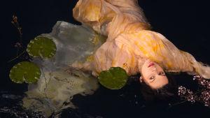 En mörkhårig kvinna som ligger i vattnet bland näckrosblad.