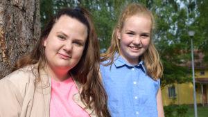 Mie Frostdahl och Felicia Sundström fotad vid ett träd.