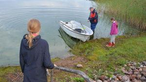 Två barn ser på när en äldre man puttar ut en plastbåt i sjön Dragsfjärden.