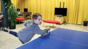 En pojke spelar bordtennis.