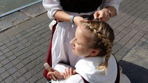 En flicka i folkdräkt får sitt hår flätat av en kompis.