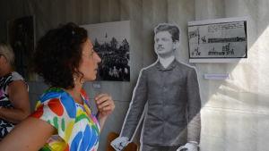 en kvinna står och tittar på ett fotokonstverk i en container