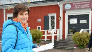 Jonna Engström-Öst står med en bunt papper i handen. I bakgrunden skymtar en röd byggnad.