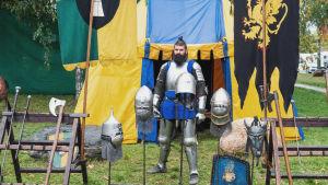 Haarniskaan pukeutunut mies seisoo keltasinisen teltan edustalla, edessään erilaisia keskiaikaisia aseita ja kypäriä.