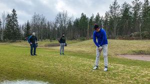 Tre män står på en golfbana, en puttar medan de andra ser på.