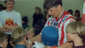Jan Rönnberg skriver autografer.